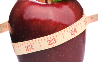 Measurement tape wrapped around red apple